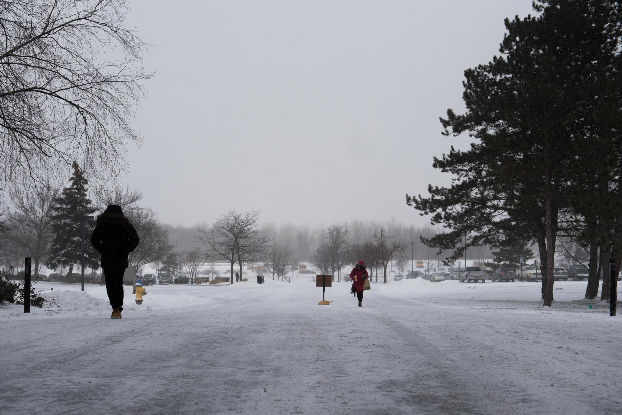 Pedestrians walk up the sidewalk on the north side of RIT's campus in front of Booth and Gannett halls on Feb. 13, 2016. Photograph by Kristen McNicholas.