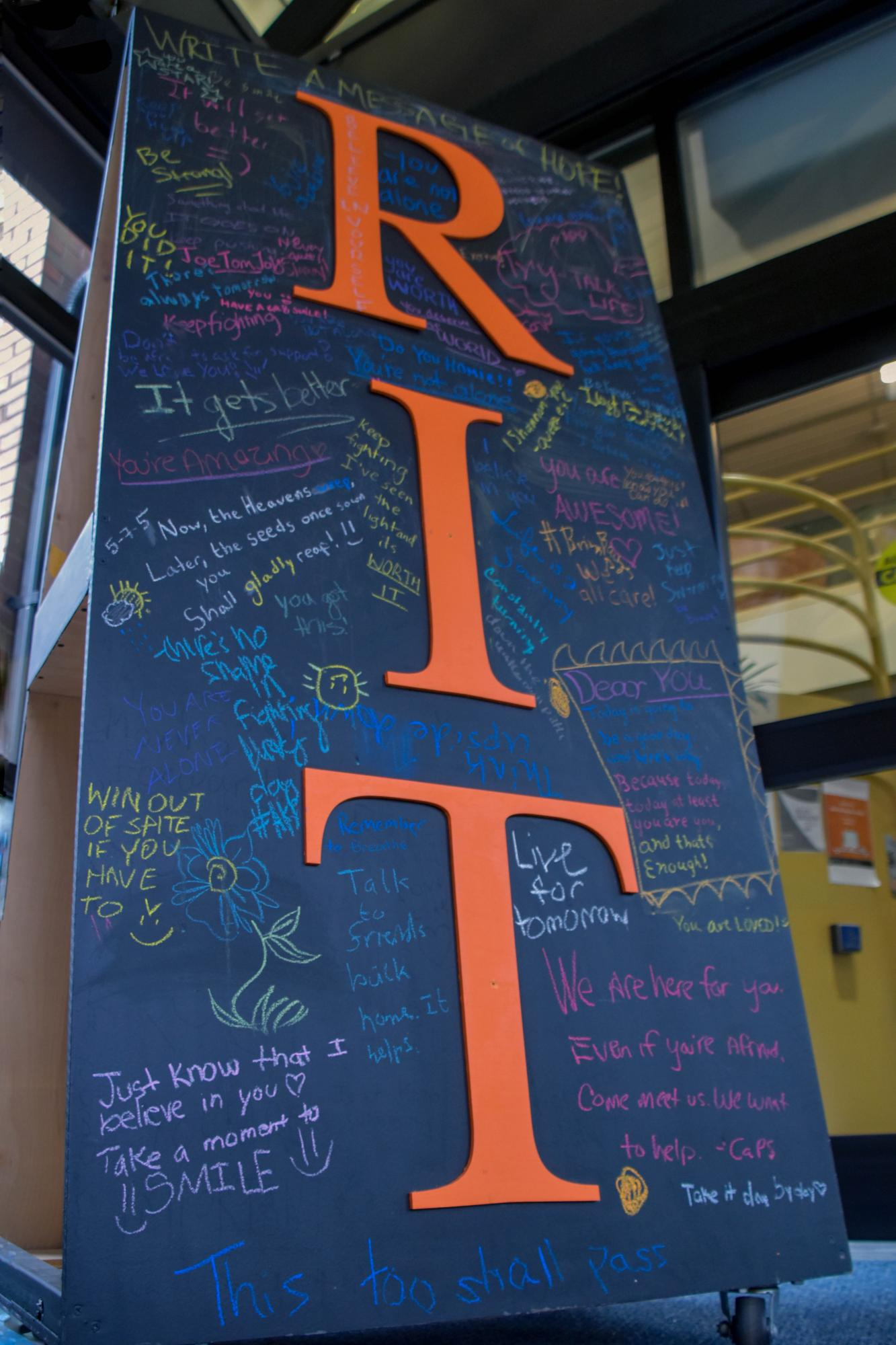 A blackboard outside August Center in Henrietta, N.Y. on Dec. 11, 2018. It is filled with filled with positive quotes written by students at RIT. Photo by Tony Wen
