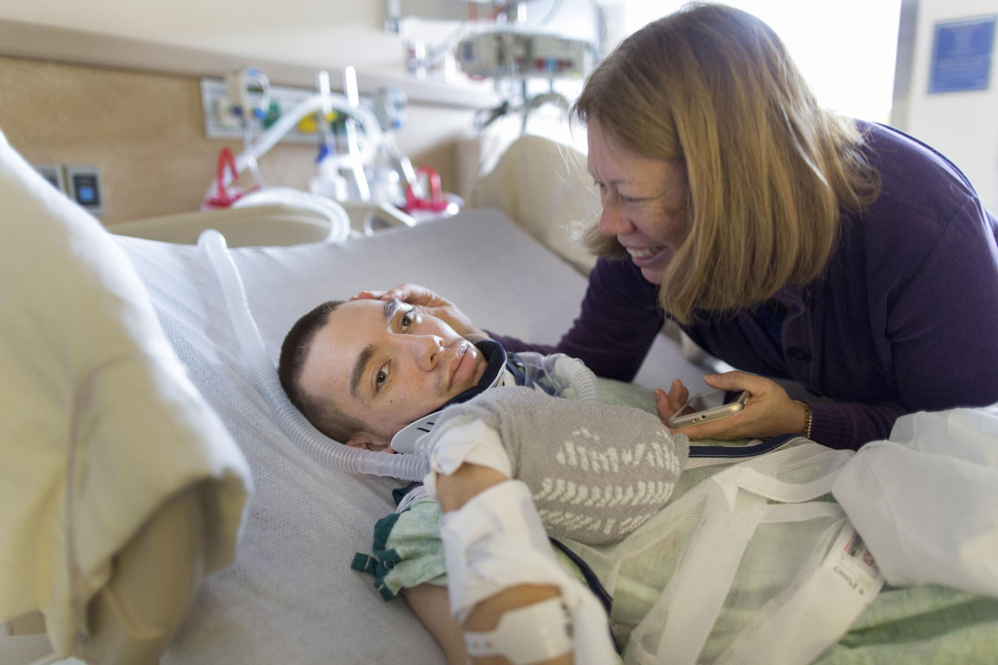 "Sarah Clemens reacts when her son Chris Clemens, 21, mouths ""good morning"" at the Strong Memorial Hospital in Rochester, N.Y. on Mar. 3, 2016. When Chris was hit by two cars on Feb. 13, 2016 he suffered a Diffused Axonal Injury in his brain and was in a coma until Mar. 2. He is part of the 10% of DAI patients that wake up.  Photography by Dominique Hessert."