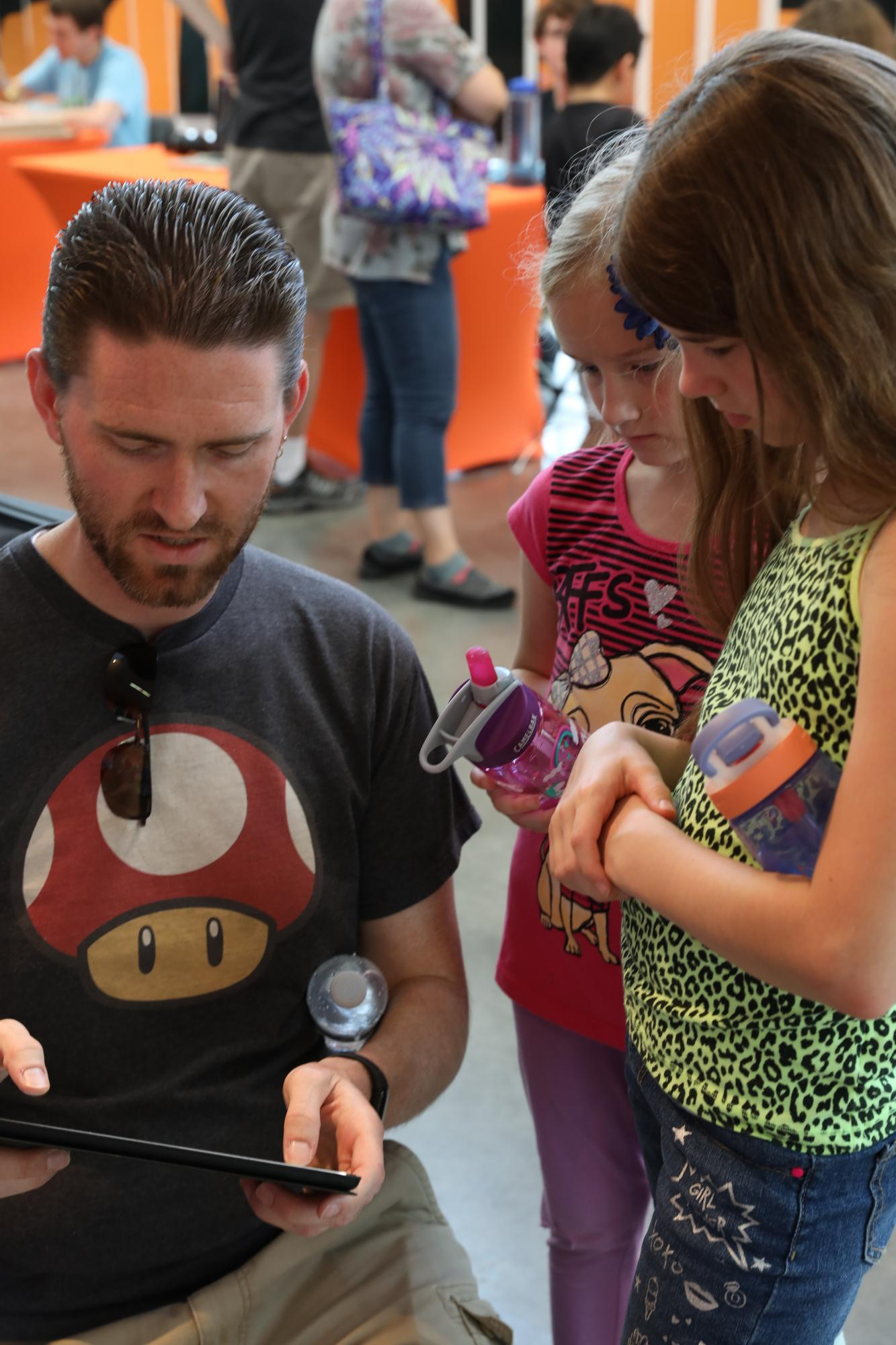 Matt Loachman, an RIT alumni, plays the video game, Crazy Platez, with his daughters Jaci (9) and Ada (6) at the Rochester Game Festival at the Gene Polisseni Center in Henrietta, N.Y. on Sept. 15, 2018. Photo by Cheyenne Boone