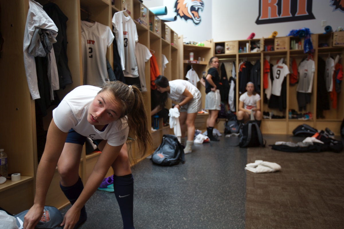 Kelly Rogers gets ready for her soccer game against Potsdam in the RIT locker room.
